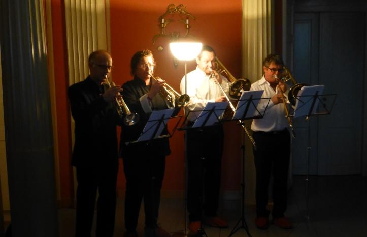 Messingkvartett fra Eidsvoll Janitsjarkorps underholder i vestibylen med tidsriktig musikk
